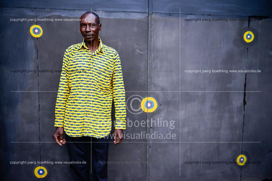 BURKINA FASO, Ouagadougou, man in yellow shirt in front of steel gate with yellow dots