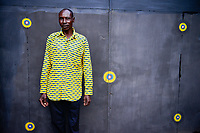 BURKINA FASO, Ouagadougou, man in yellow shirt in front of steel gate with yellow dots