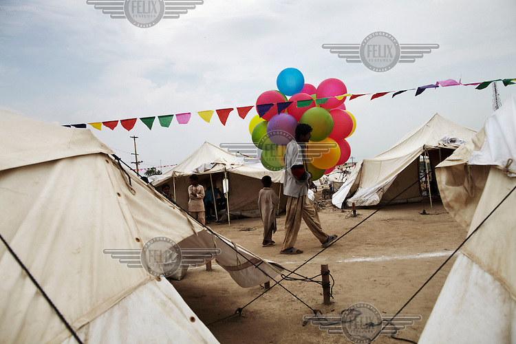 A man sells balloons to celebrate Eid at an IDP (internally displaced persons) camp set up by UNHCR (United Nations High Commission for Refugees) for those affected by the flooding. Severe flooding had left at least 1,600 people dead and affected up to 20 million.