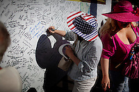 """Phoenix, Arizona, March 27, 2010 - Supporters sign a traveling board during the third rally of the 20-day Tea Party Express tour form a Tea Party bus window at the Arizona capital. The board, which was created by Bob Root, is being signed by supporters all along the tour, including Sarah Palin (in blue) which says, """"God Bless us all, Thank You, Sarah."""" The tour which began in Searchlight, NV, hometown of Senate Majority Leader Harry Reid, will wind through the United States ending up in Washington, D.C. on April 15 for a tax day rally. ."""