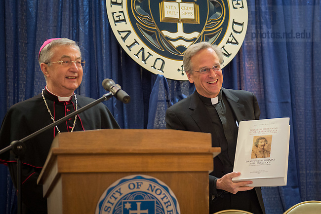 "May 9, 2016; Archbishop Jean-Louis Brugues, Archivist and Librarian of the Holy Roman Church, presents University of Notre Dame President Rev. John I. Jenkins, C.S.C. with a gift at a ceremony where Archbishop Brugues and Fr. Jenkins signed a memorandum of understanding for collaboration and exchanges between the Vatican Library and Notre Dame.  The signing ceremony was in conjunction with the conference ""The Promise of the Vatican Library,"" an international academic conference highlighting the holdings of the Vatican Library and opportunities for future research.(Photo by Matt Cashore/University of Notre Dame)"