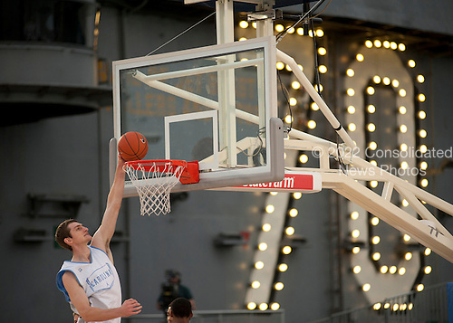 University of North Carolina basketball player Tyler Zeller dunks during a practice Thursday, November 10, 2011 in the basketball arena on the flight deck aboard Nimitz-class aircraft carrier USS Carl Vinson (CVN 70) in San Diego, California. Carl Vinson is hosting Michigan State University and the University of North Carolina for the inaugural Quicken Loans Carrier Classic basketball game on Veteran's Day, November 11.  United States President Barack Obama and first lady Michelle Obama are scheduled to attend the game..Mandatory Credit: James R. Evans - U.S. Navy via CNP