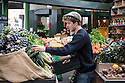 London, UK. 15.11.2014. Young male stallholder arranges leeks on his stall at Borough Market. Photograph © Jane Hobson.