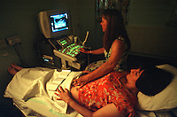 Midwife performing an ultrasound scan during an ante-natal examination. This equipment allows the midwife to monitor the baby's position, its growth and heart rate. The examination is taking place on an almost full term pregnant mother to be. This image may only be used to portray the subject in a positive manner..©shoutpictures.com..john@shoutpictures.com