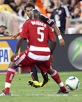 Andy Najar #14 of D.C. United slips the ball past Jair Benitez #5 of FC Dallas during an MLS match at RFK Stadium in Washington D.C. on August 14 2010. Dallas won 3-1.