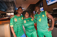 Hartford, CT - Friday June 13, 2014: Cameroonian Joyce Ashuntantang watches the Cameroon vs. Mexico FIFA World Cup first round match with her son's George (left) and David Abunaw at Damons Tavern in Hartford, CT.