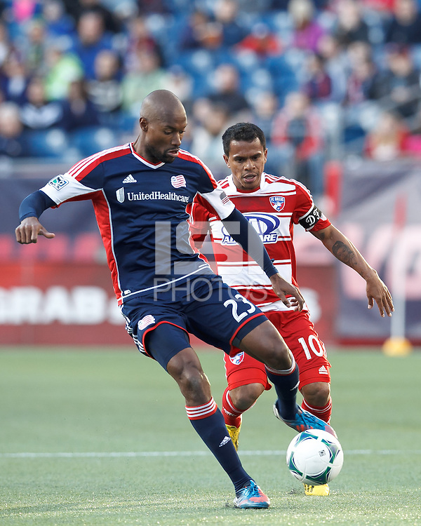 New England Revolution defender Jose Goncalves (23) intercepts long pass to FC Dallas midfielder David Ferreira (10)..  In a Major League Soccer (MLS) match, FC Dallas (red) defeated the New England Revolution (blue), 1-0, at Gillette Stadium on March 30, 2013.