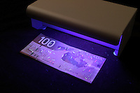 2004 File Photo - <br /> A Counterfeit Bill Detector is used to check the new design of Canadian hundred dollars bill.