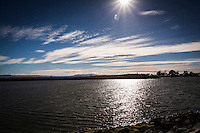 The sun beams down from a blue sky with streaks of white clouds, then reflects in the waters of the small boat lagoon at San Leandro Marina Park along San Francisco Bay.