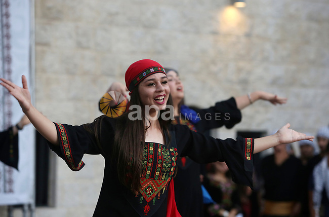 Palestinian Dabka dancers wear a traditional costumes, perform during a festival marking Traditional Palestinian Dress Day, in the West Bank city of Nablus on August 22, 2017. Photo by Ayman Ameen