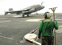 "060518-N-7981E-041 Pacific Ocean (May 18, 2006)- A member of V-2 Arresting Gears stands ready to guide arresting cable back into place as an EA-6B Prowler of Electronic Attack Squadron One (VAQ) 131 ""Lancers"" lands aboard the Nimitz-class aircraft carrier USS Abraham Lincoln (CVN-72) during flight operations. Lincoln and embarked Carrier Air Wing (CVW) 2 are currently underway in the Western Pacific operating area. U.S. Navy photo by Photographer's Mate Airman James R. Evans (RELEASED)"
