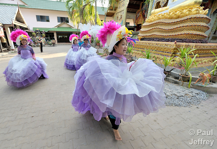 Members of a girl's dance group organized by the Hualin Buddhist Temple in the northern Thailand village of Toong-sa-tok prepare for a performance. The group, which performs for weddings and other celebrations and uses the proceeds for its members' educational expenses, includes orphans and other vulnerable girls, many of them affected by HIV and AIDS.