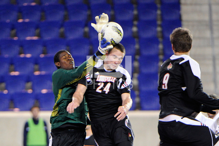 Connecticut Huskies goalkeeper Andre Blake (18) takes the ball off the head of Austin Berry (24) of the Louisville Cardinals. Connecticut defeated Louisville 1-0 during the first semifinal match of the Big East Men's Soccer Championships at Red Bull Arena in Harrison, NJ, on November 11, 2011.