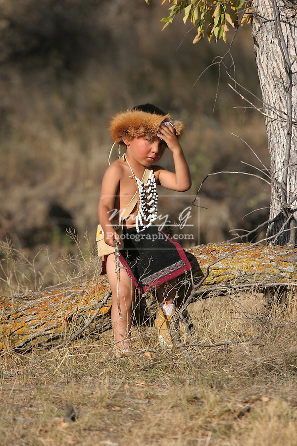 A young Native American Indian boy sitting on a log