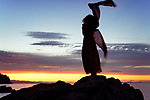 Artistic dynamic photograph of a woman back dark silhouette in long red dress dancing on the rocks of an ocean shore in the wind in sunset sky scenery