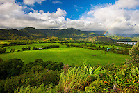 Early morning in the Hanalei Valley; as showers pass over the town a rainbow forms over Hanalei Bay, Kauai.