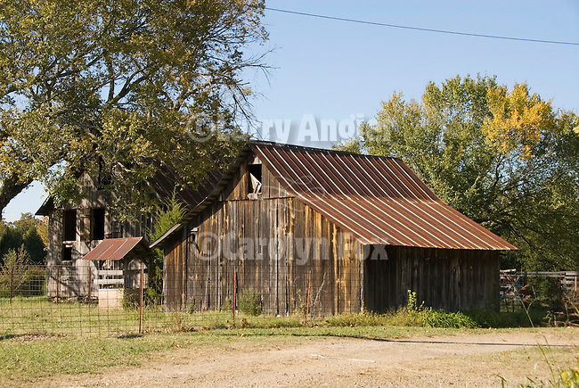Wooden barn with rusting metal roof along the road in Arkansas.