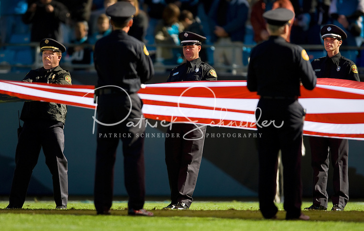 Members of the Charlotte Fire Department stretch out a giant American Flag prior the game during an NFL football game at Bank of America Stadium in Charlotte, NC.