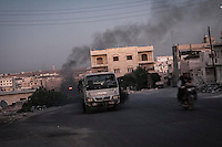 In this Wednesday, Oct. 09, 2013 photo, smoke rises from burning tires used by opposition fighters to thicken the air in order to avoid being targeted by aircraft and artillery shelling as Syrian civilians drive through empty streets in Maraat Al-Nouman in the Idlib province countryside of Syria. (AP/Photo)