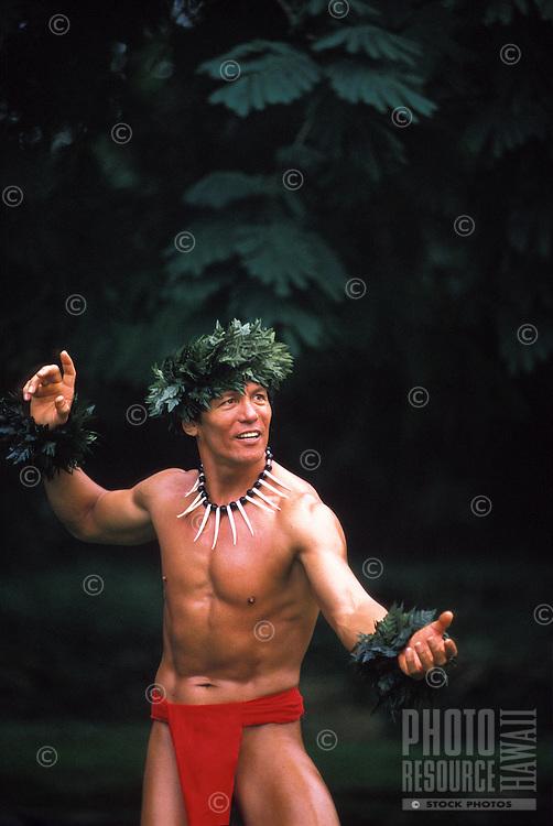 Hawaiian warrior hula dancer in red loin cloth with green leaf leis on head and wrist
