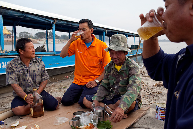 """Thai tour boat operators from left, Mon, Peng, Noi, and Bounsri drink Lao beer and whiskey on a beach in Myanmar on the Mekong River near Sop Ruak, Thailand. """"Some times business is not good because the water is low from the dams in China that we have to take boats out,"""" Bounsri said. Photo taken on Thursday, December 10, 2009. Kevin German / Luceo Images"""