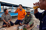"Thai tour boat operators from left, Mon, Peng, Noi, and Bounsri drink Lao beer and whiskey on a beach in Myanmar on the Mekong River near Sop Ruak, Thailand. ""Some times business is not good because the water is low from the dams in China that we have to take boats out,"" Bounsri said. Photo taken on Thursday, December 10, 2009. Kevin German / Luceo Images"