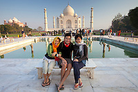 Tourists sit on Diana bench at The Taj Mahal mausoleum southern view with reflecting pool, Uttar Pradesh, India