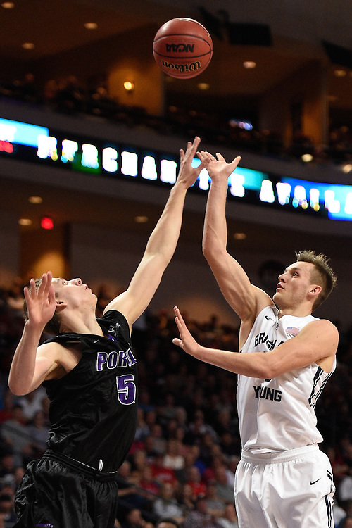 March 9, 2015; Las Vegas, NV, USA; Brigham Young Cougars guard Kyle Collinsworth (5) shoots the basketball against Portland Pilots forward/center Volodymyr Gerun (52) during the first half of the WCC Basketball Championships at Orleans Arena.