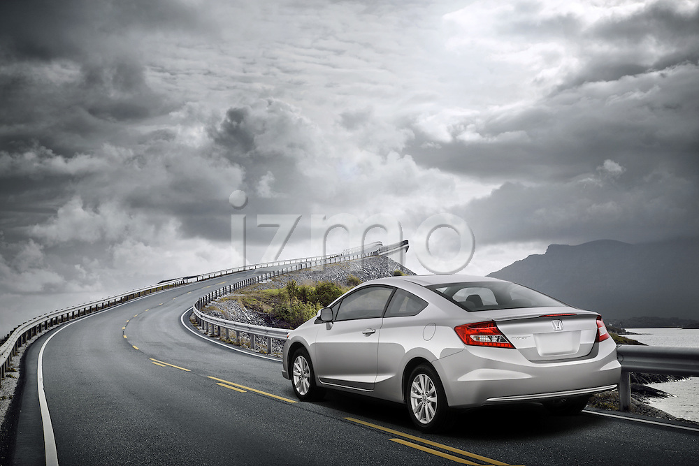 One silver 2012 Honda Civic Coupe EX driving on road during stormy day.