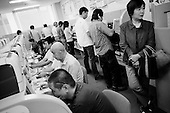 Toyota City, Japan.June 15, 2009..Toyota City, the Detroit of Japan, and home of Toyota car manufacturing company. Toyota unemployment office...Laid-off short-term temporary workers who used to work at a Toyota plant or Toyota related plants search computers for work and wait in line for benefits at Toyota unemployment office.