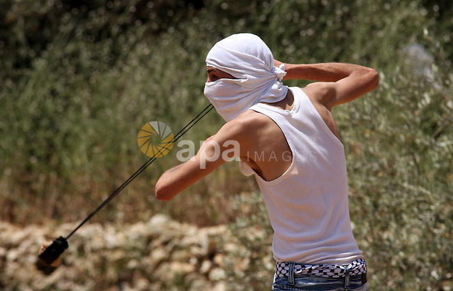 A Palestinian youth uses a sling to hurl stones at Israeli soldiers during clashes in the West  Bank village of Nabi Saleh, on 28 May 2010. Palestinians protest weekly against the neighbouring Jewish settlement of Halamish. photo by Eyad Jadallah