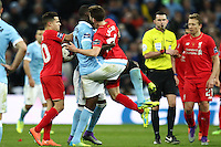 Yaya Toure of Manchester City throws Adam Lallana of Liverpool to the floor while Fernandinho of Manchester City grabs Lallana round the neck during the Capital One Cup match between Liverpool and Manchester City at Wembley Stadium, London, England on 28 February 2016. Photo by David Horn / PRiME Media Images.