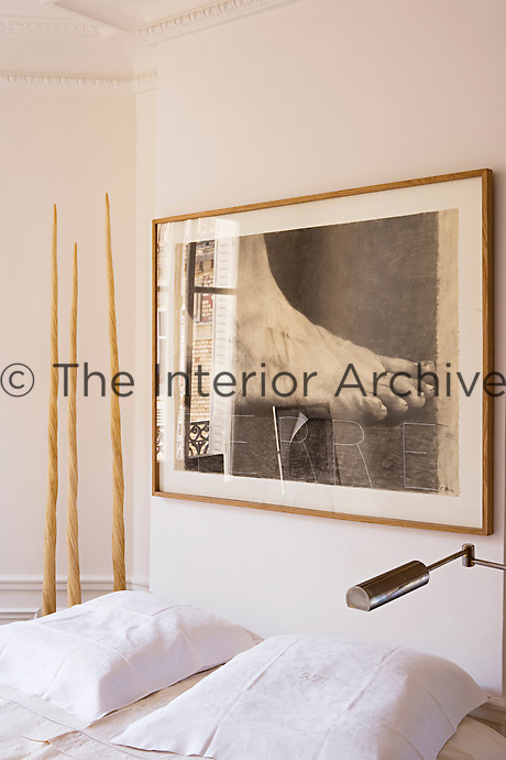In the bedroom the sculptural forms of three Narwhal tusks are situated next to the double bed above which hangs a large print of a foot