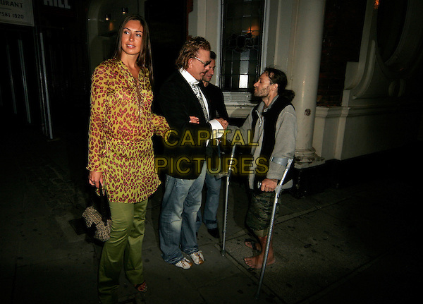 MICKEY ROURKE & GIRL.Leaving The Wellington Club.August 17th, 2005.full length arms linked jeans denim homeless crutches shaking hands animal print yellow top.www.capitalpictures.com.sales@capitalpictures.com.©Capital Pictures.