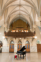 A huge Gothic church that has been converted into a social hall and concert venue is featured in this image along with its resident black grand piano, waiting for the moment when someone will play it. The high vaulted ceiling with arches and the three door symmetry focus the eye on the battery of large organ pipes in the choir loft...here is some genuine and grand beauty in religious architecture. <br />
