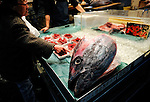 An elderly woman buys blue fin tuna at a retailer inside the world's largest fish and marine products market in Tsukiji, Tokyo on Monday 30 March 2009.