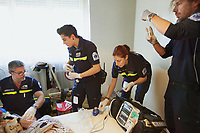 Switzerland. Canton Ticino. Breganzona. A senior woman is lying down on her bed. The elderly woman is suffering from a pneumonia and severe respiratory problems. She needs to be brought to hospital for medical examinations. The emergency doctor Daniele Speciale (L) is working with three paramedics. They all work for the Croce Verde Lugano. They wear blue uniforms and medical gloves. The man (R) and the woman (center left) are professional certified nurses, the other woman (center right) is a volunteer specifically trained in emergency rescue. The doctor needs to intubate the patient in order to improve her oxygen flow. Tracheal intubation, usually simply referred to as intubation, is the placement of a flexible plastic tube into the trachea (windpipe) to maintain an open airway and is frequently performed in critically injured, ill, or anesthetized patients to facilitate ventilation of the lungs, including mechanical ventilation, and to prevent the possibility of asphyxiation or airway obstruction. A monitor is laid on the bed and controls the patient's vital functions, such as electrocardiogram, blood pressure's measurement, respiratory rate and pulse oximetry (oxygen saturation). On the woman's arm, an intravenous infusion with saline solution will be fixed. The Croce Verde Lugano is a private organization which ensure health safety by addressing different emergencies services and rescue services. Volunteering is generally considered an altruistic activity where an individual provides services for no financial or social gain to benefit another person, group or organization. Volunteering is also renowned for skill development and is often intended to promote goodness or to improve human quality of life. Medical gloves are made of different polymers including latex, nitrile rubber, polyvinyl chloride and neoprene. Pneumonia is an inflammatory condition of the lung. Breganzona is a quarter of the city of Lugano.13.01.2018 © 2018 Didier Ruef