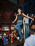 SINGAPORE, female bartenders dancing in CU Nightclub bar.