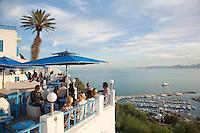 People sitting on terrace overlooking marina and Gulf of Tunis, Sidi Bou Said, Tunisia