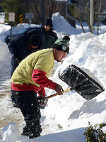 Jonathan Figueroa of Trenton, New Jersey shovels snow from the sidewalk while cleaning up after Winter Storm Jonas Sunday January 24, 2016 in Newtown, Pennsylvania. (Photo by William Thomas Cain)