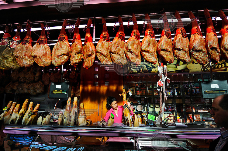 A young woman slices jamon at a stall devoted to Jamon Iberico, in Valencia's Mercado Central. These hams, also called Pata Negra, are prized for their taste and texture, coming from wild pigs raised on acorns.