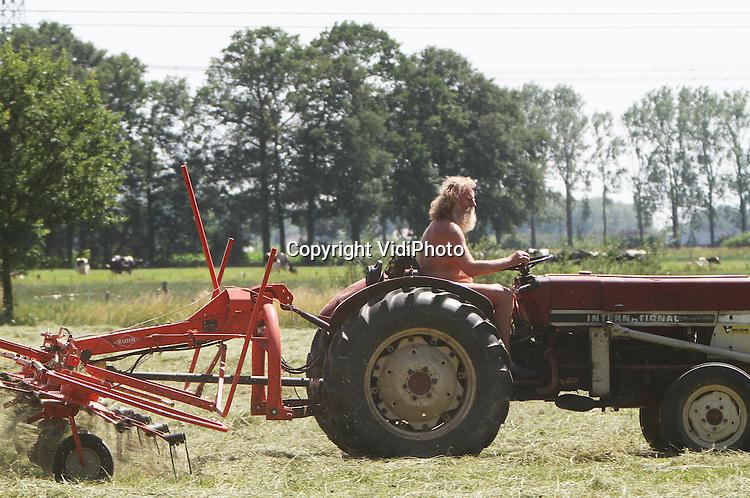 Foto: VidiPhoto..HEMMEN - De plotseling omslag naar tropische warmte is wel even wennen. Met deze temperaturen is het voor agrariërs een perfecte dag om het gras te schudden. En wat is er dan aangenamer om dat te doen in je korte broek en blote lijf, zoals deze boer in het Betuwse Hemmen bij Dodewaard.