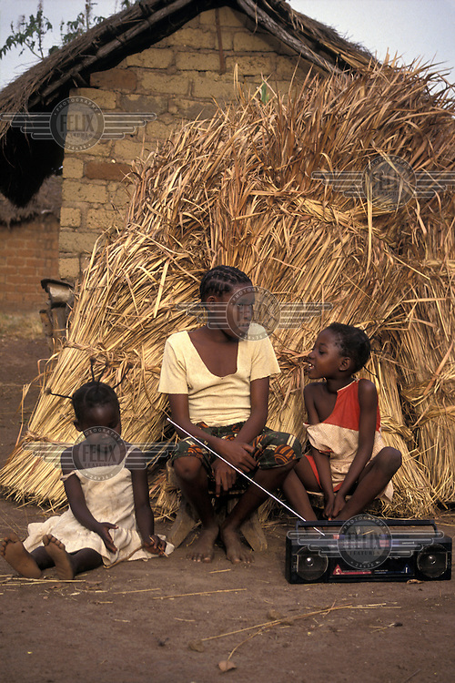 Children istening to the radio in a small village.