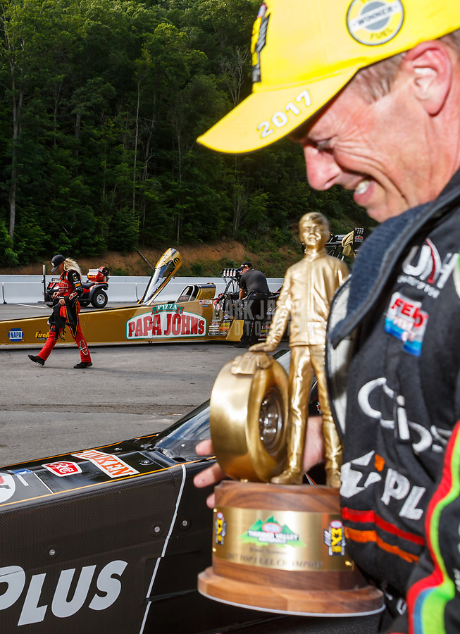 Jun 18, 2017; Bristol, TN, USA; NHRA top fuel driver Leah Pritchett (left) walks to her tow vehicle as Clay Millican celebrates after winning the Thunder Valley Nationals at Bristol Dragway. Mandatory Credit: Mark J. Rebilas-USA TODAY Sports