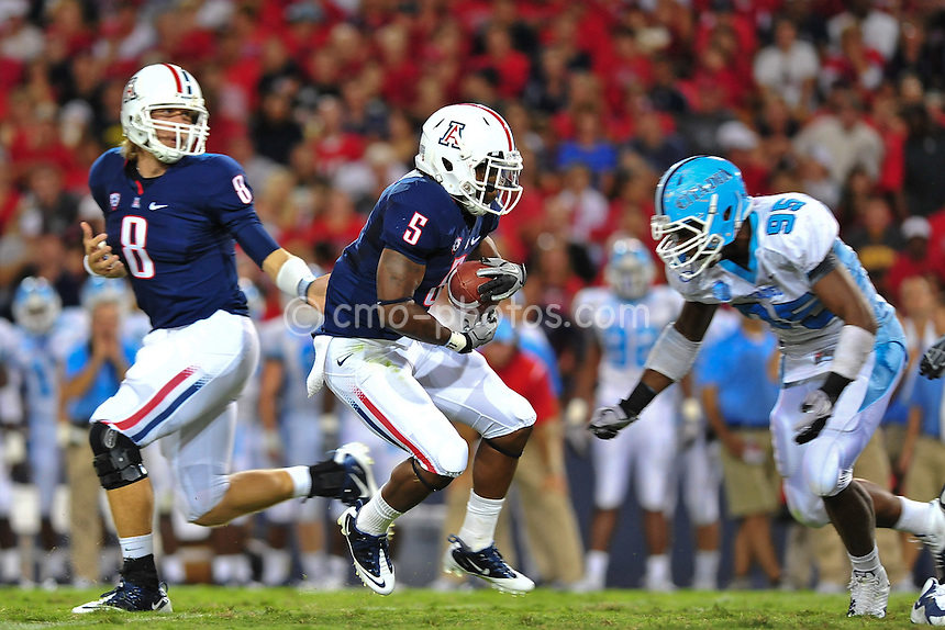 Sept 11, 2010; Tucson, AZ, USA; Arizona Wildcats running back Nic Grigsby (5) is met in the backfield by Citadel Bulldogs defensive end Erik Clanton (95) after taking the handoff from quarterback Nick Foles (8) in the 2nd quarter of a game at Arizona Stadium. Arizona won the game 52-6.