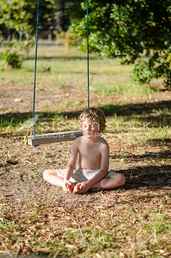 Young boy sitting cross-legged and meditating / praying on the ground in summer, New Zealand - stock photo, canvas, fine art print