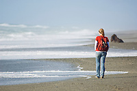 female tourist walking on isolated west coast beach near lake Mahinapua, New Zealand
