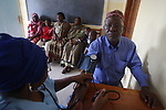 TANGA, TANZANIA - JULY 7:   Familes sit inside a clinic run by an Non-Governmental Organization for two days waiting for treatment and medicine on July 7, 2010 in Tanga, Tanzania. The Tanzanian health care system has seen a gradual decline with low medical staff morale due to declining wages and operational difficulties in the central medical stores and domestic pharmaceuticals industries.