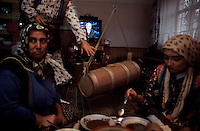 Butter churn in middle of Cepne Living Room..Cepne people are members of a Turkic tribe and haven't changed dress or speech radically since migration from central Asia.  But now electric power is coming to this Yayla.  So they still do hand labor and have butter churns in the middle of their camps, but now they have TV blaring in the background.