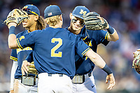 Michigan Wolverines third baseman Blake Nelson (10) hugs teammate Jack Blomgren (2) in between innings during Game 6 of the NCAA College World Series against the Florida State Seminoles on June 17, 2019 at TD Ameritrade Park in Omaha, Nebraska. Michigan defeated Florida State 2-0. (Andrew Woolley/Four Seam Images)
